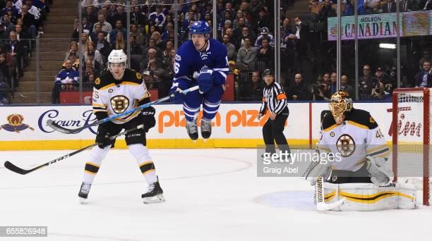 Mitch Marner of the Toronto Maple Leafs jumps in front of Tuukka Rask of the Boston Bruins as Brandon Carlo of the Boston Bruins defends during the...