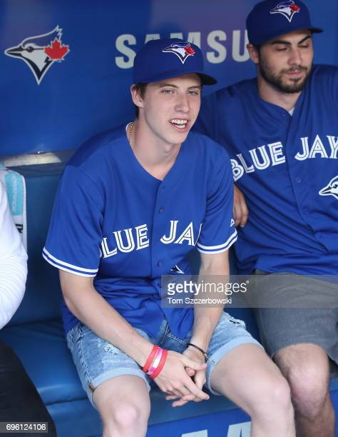Mitch Marner of the Toronto Maple Leafs looks on from the dugout before throwing out the first pitch before the start of the Toronto Blue Jays MLB...