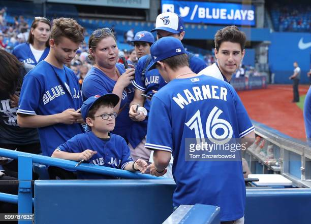 Mitch Marner of the Toronto Maple Leafs signs autographs for fans before the start of the Toronto Blue Jays MLB game against the Tampa Bay Rays at...