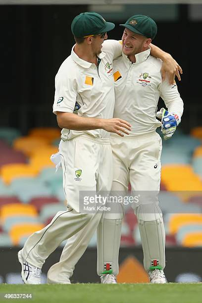 Mitch Marsh and Peter Nevill of Australia celebrate victory during day five of the First Test match between Australia and New Zealand at The Gabba on...