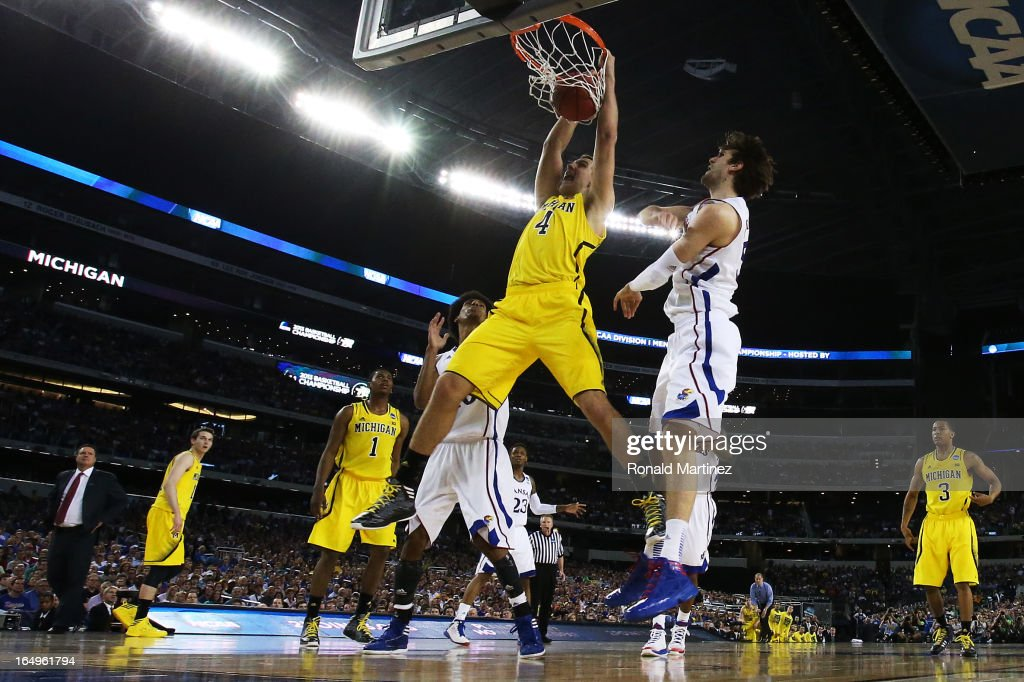 Mitch McGary #4 of the Michigan Wolverines dunks pask <a gi-track='captionPersonalityLinkClicked' href=/galleries/search?phrase=Jeff+Withey&family=editorial&specificpeople=6669172 ng-click='$event.stopPropagation()'>Jeff Withey</a> #5 of the Kansas Jayhawks in the first half during the South Regional Semifinal round of the 2013 NCAA Men's Basketball Tournament at Dallas Cowboys Stadium on March 29, 2013 in Arlington, Texas.
