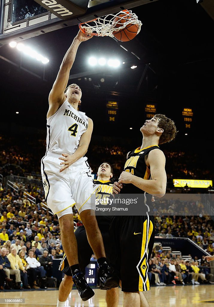 Mitch McGary #4 of the Michigan Wolverines gets in for a first half dunk next to Adam Woodbury #34 of the Iowa Hawkeyes at Crisler Center on January 6, 2013 in Ann Arbor, Michigan.
