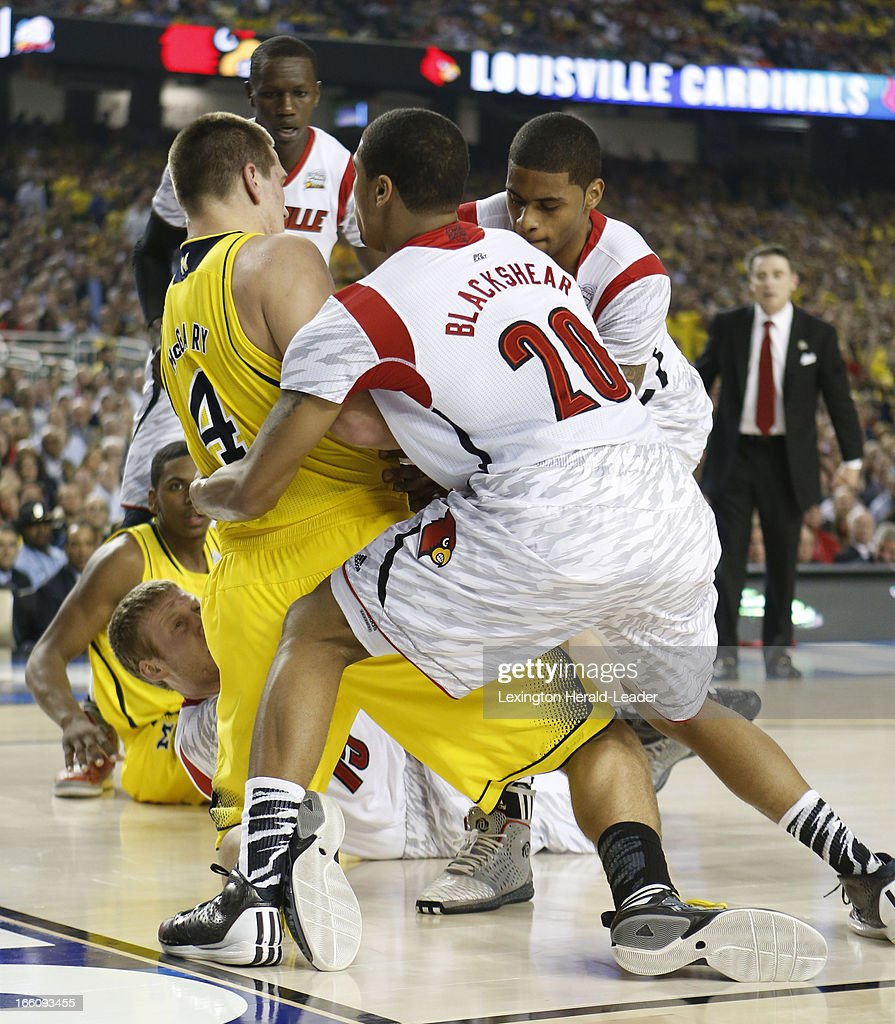 Mitch McGary (4) of the Michigan Wolverines gets ties up by several Louisville players during first-half action in the NCAA Tournament final at the Georgia Dome in Atlanta, Georgia, Monday, April 8, 2013.