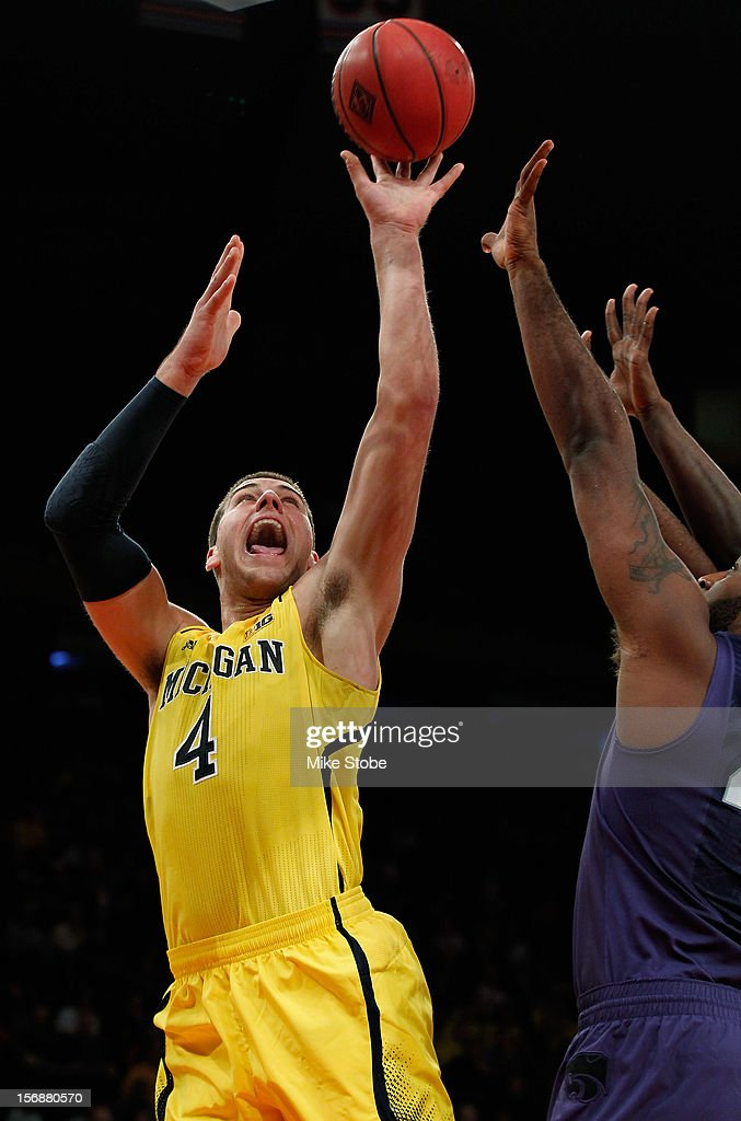 Mitch McGary #4 of the Michigan Wolverines hits a basket over the reach of Thomas Gipson #42 of the Kansas State Wildcats at Madison Square Garden on November 23, 2012 in New York City. Michigan Wolverines defeated Kansas State Wildcats 71-57.