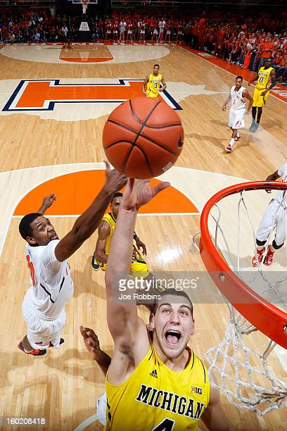 Mitch McGary of the Michigan Wolverines rebounds against Myke Henry of the Illinois Fighting Illini during the game at Assembly Hall on January 27...