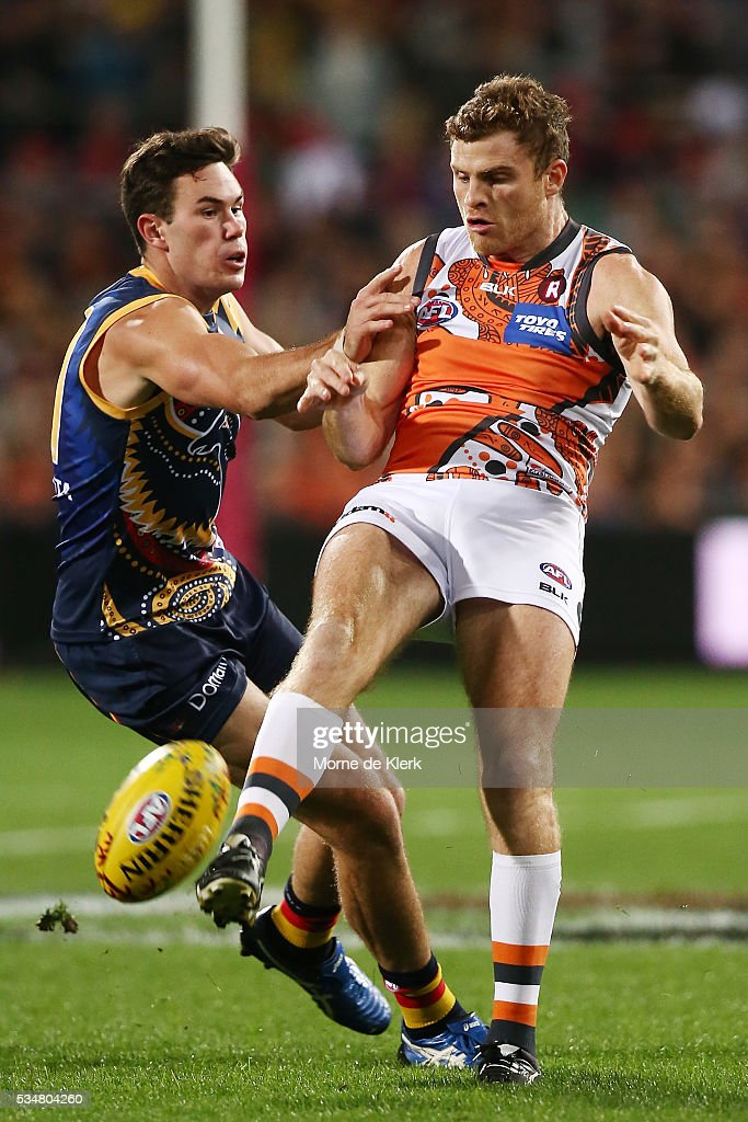 Mitch McGovern of the Crows attempts a tackle as Heath Shaw of the Giants kicks the ball during the round 10 AFL match between the Adelaide Crows and the Greater Western Sydney Giants at Adelaide Oval on May 28, 2016 in Adelaide, Australia.