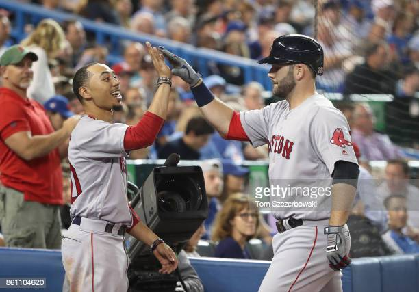 Mitch Moreland of the Boston Red Sox is congratulated by Mookie Betts after hitting a tworun home run in the seventh inning during MLB game action...