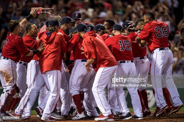 Mitch Moreland of the Boston Red Sox is mobbed by teammates after hitting a walkoff solo home run during the eleventh inning of a game against the...