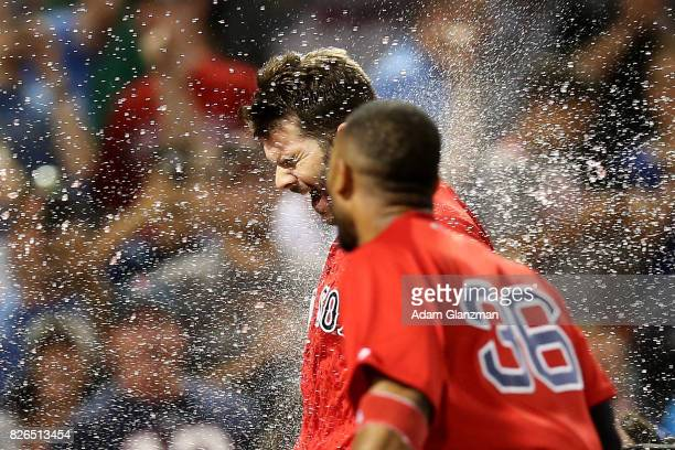 Mitch Moreland of the Boston Red Sox is swarmed by teammates at home plate after hitting a walk off solo home run in the eleventh inning of a game...