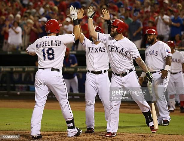 Mitch Moreland of the Texas Rangers is congratulated by Mike Napoli for hitting a three run home run for Choo and Fielder to score in the third...