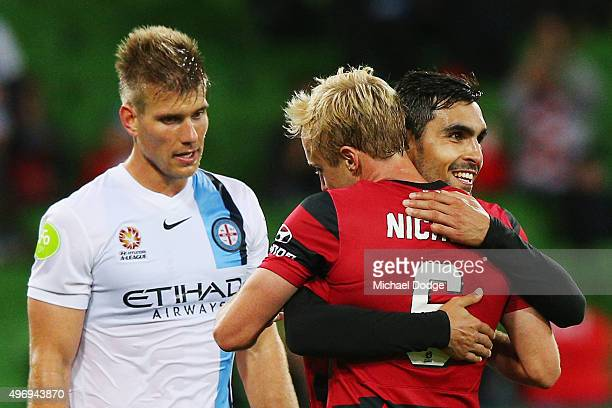 Mitch Nichols of the Wanderers and Dimas Delgado celebrate the win next to Erik Paartalu of Melbourne City during the round six ALeague match between...