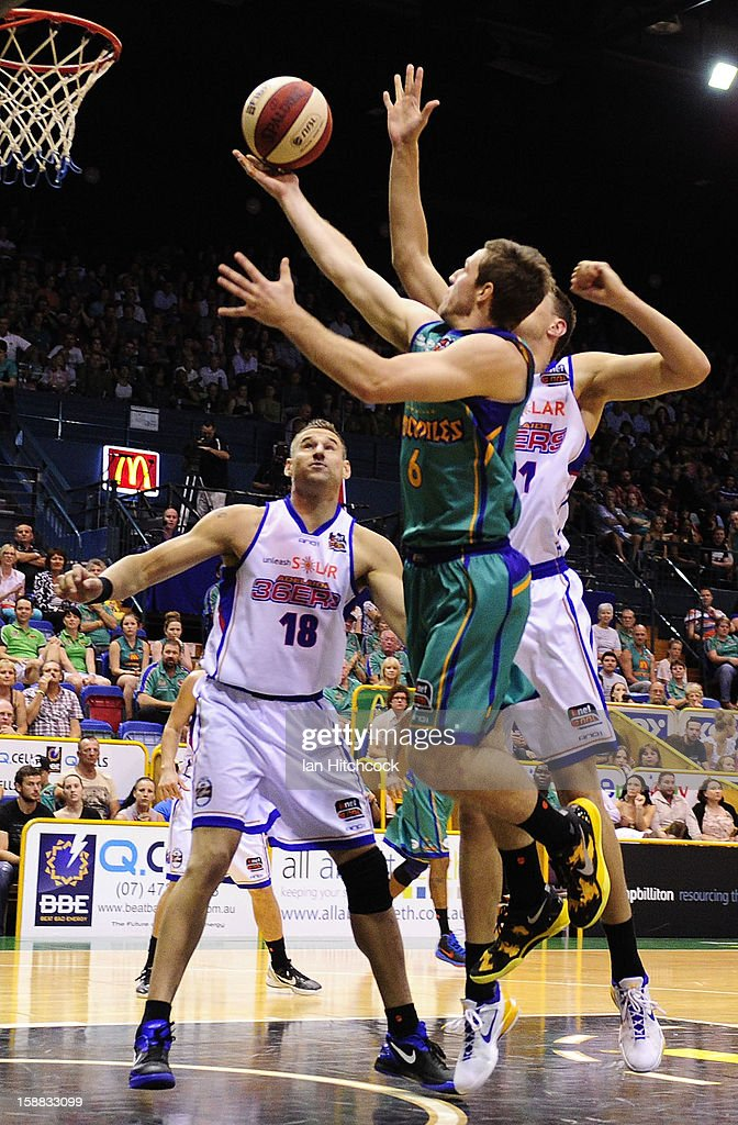 Mitch Norton of the Crocodiles goes for a layup past Pero Vasiljevic of the 36ers during the round 12 NBL match between the Townsville Crocodiles and the Adelaide 36ers at Townsville Entertainment Centre on December 31, 2012 in Townsville, Australia.