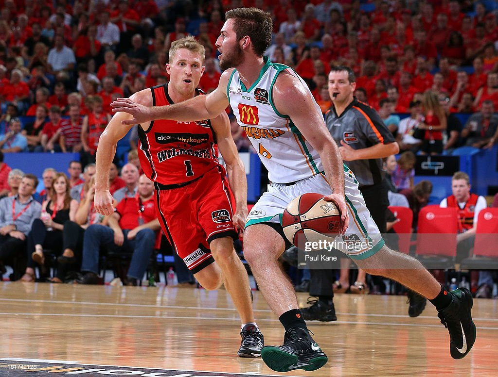 Mitch Norton of the Crocodiles works the ball up the court against Rhys Carter of the Wildcats during the round 19 NBL match between the Perth Wildcats and the Townsville Crocodiles at Perth Arena on February 15, 2013 in Perth, Australia.