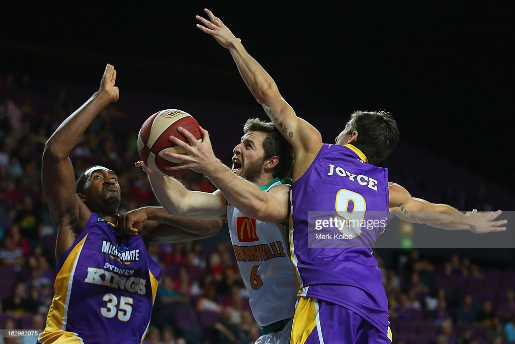 Mitch Norton of the Crocs shoots under pressure from Darnell Lazare and Dan Joyce of the Kings during the round 21 NBL match between the Sydney Kings and the Townsville Crocodiles at Sydney Entertainment Centre on March 3, 2013 in Sydney, Australia.
