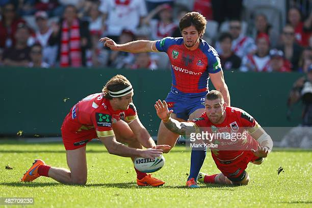 Mitch Rein and Josh Dugan of the Dragons dives for the ball under pressure from Jake Mamo of the Knights as Mitch Rein scores a try during the round...