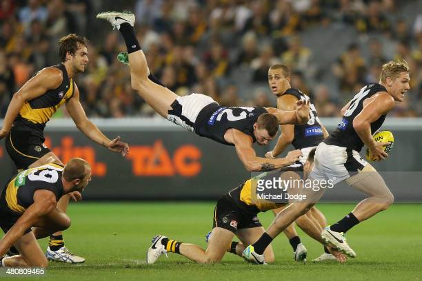 Mitch Robinson of the Blues is propelled into the air after colliding with Trent Cotchin of the Tigers as teamate Tom Bell runs with the ball during...