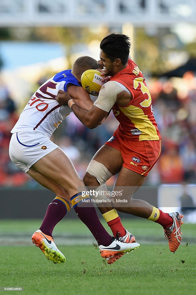 Mitch Robinson of the Lions competes for the ball against Aaron Hall of the Suns during the round 16 AFL match between the Gold Coast Suns and the...