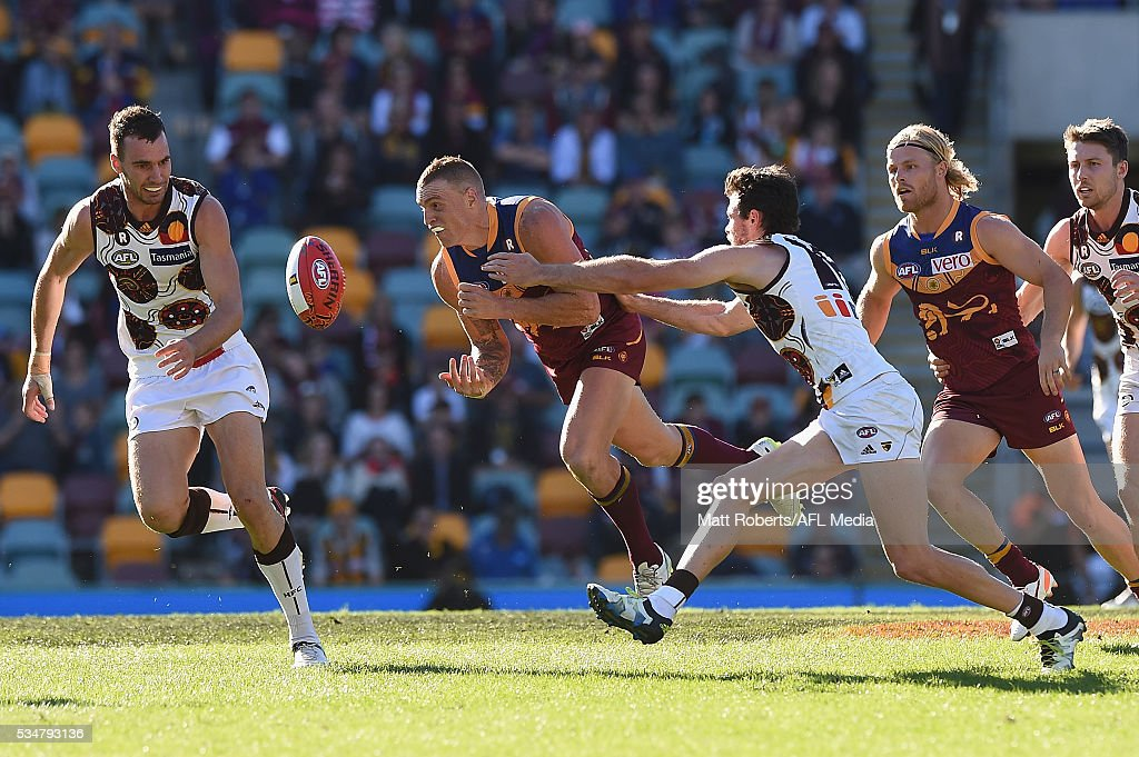 Mitch Robinson of the Lions handballs under pressure during the round 10 AFL match between the Brisbane Lions and the Hawthorn Hawks at The Gabba on May 28, 2016 in Brisbane, Australia.
