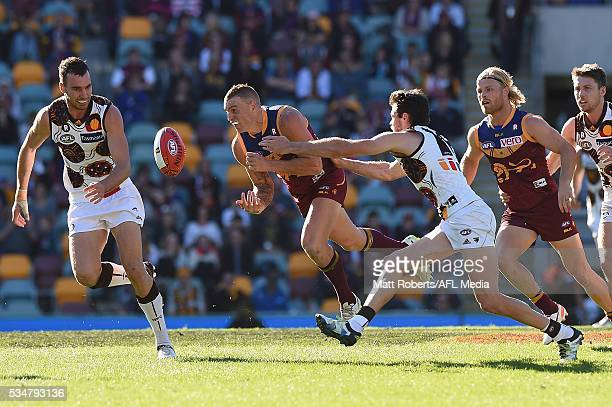 Mitch Robinson of the Lions handballs under pressure during the round 10 AFL match between the Brisbane Lions and the Hawthorn Hawks at The Gabba on...