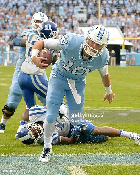 Mitch Trubisky of the North Carolina Tar Heels runs over Dwayne Norman of the Duke Blue Devils for a touchdown during their game at Kenan Stadium on...