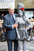 Mitch Winehouse poses as a statue of the late Amy Winehouse is unveiled in Camden Town on September 14 2014 in London England