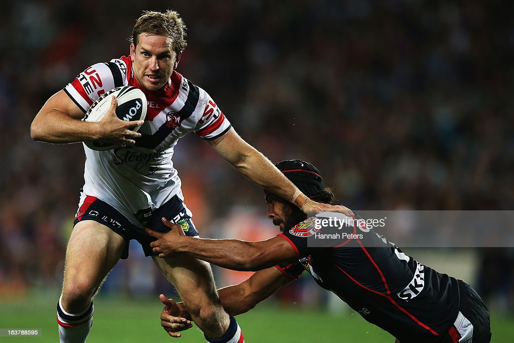 Mitchell Aubusson of the Roosters fends off Dane Nielsen of the Warriors during the round two NRL match between the New Zealand Warriors and the Sydney Roosters at Eden Park on March 16, 2013 in Auckland, New Zealand.
