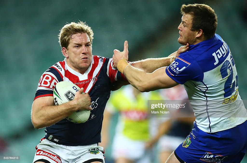 Mitchell Aubusson of the Roosters plams off <a gi-track='captionPersonalityLinkClicked' href=/galleries/search?phrase=Josh+Morris+-+Rugby+Player&family=editorial&specificpeople=10980783 ng-click='$event.stopPropagation()'>Josh Morris</a> of the Bulldogs during the round 17 NRL match between the Sydney Roosters and the Canterbury Bulldogs at Allianz Stadium on June 30, 2016 in Sydney, Australia.