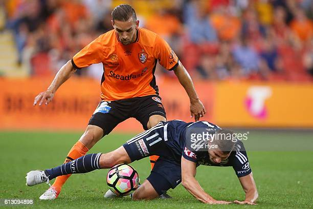 Mitchell Austin of the Victory and Jack Hingert of the Roar compete for the ball during the round one ALeague match between the Brisbane Roar and...