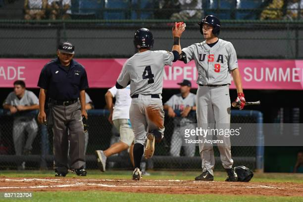 Mitchell Boe of United States celebrates a score with teammate Ben Norman during the Baseball Group B match between United States and Russia during...