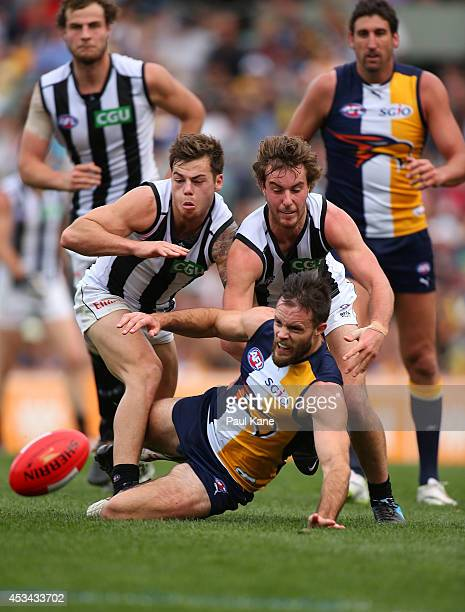 Mitchell Brown of the Eagles contest for the ball against Jamie Elliot and Tim Broomhead of the Magpies during the round 20 AFL match between the...