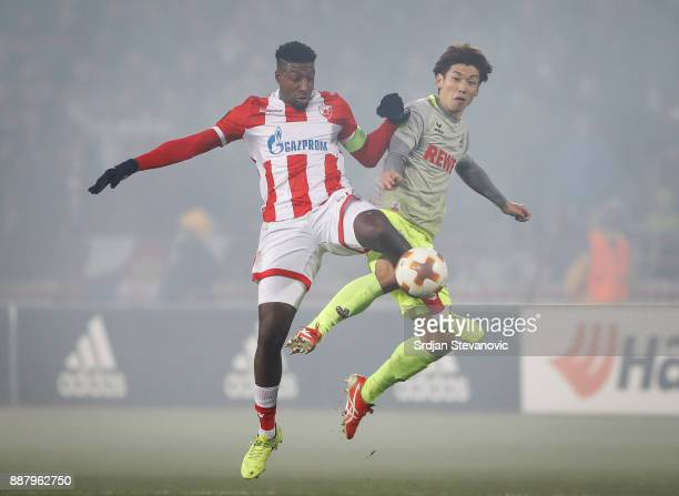 Mitchell Donald of Crvena Zvezda competes for the ball against Yuya Osako of FC Koeln during the UEFA Europa League group H match between Crvena...