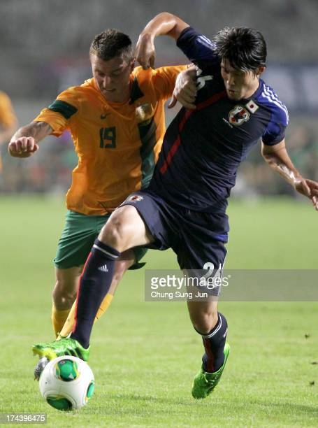 Mitchell Duke of Australia competes for the ball with Daisuke Suzuki of Japan during the EAFF East Asian Cup match between Japan and Australia at...