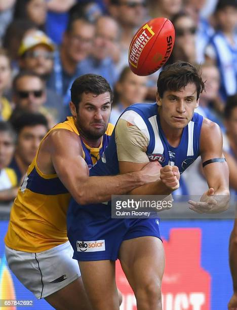Mitchell Hibbered of the Kangaroos handballs whilst being tackled by Jack Darling of the Eagles during the round one AFL match between the North...