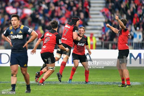 Mitchell Hunt of the Crusaders is congratulated by team mates after kicking the last minute winner during the round 15 Super Rugby match between the...