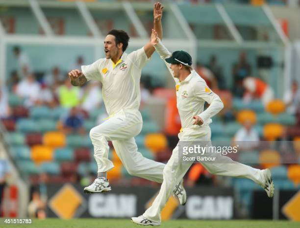 Mitchell Johnson of Australia celebrates after dismissing Jonathan Trott of England during day three of the First Ashes Test match between Australia...
