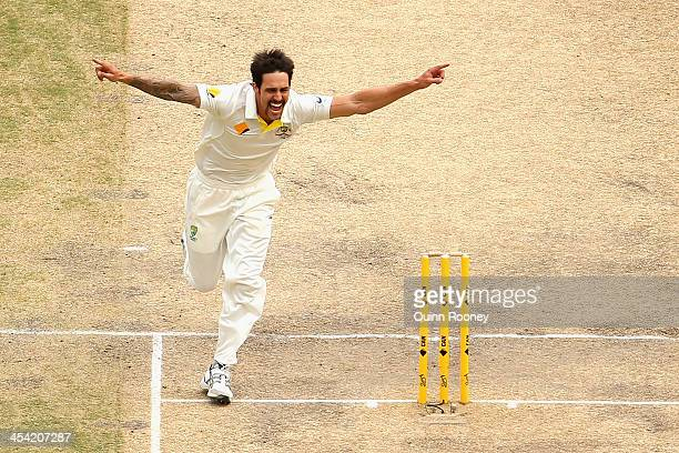 Mitchell Johnson of Australia celebrates after taking the wicket of Alastair Cook of England during day four of the Second Ashes Test Match between...