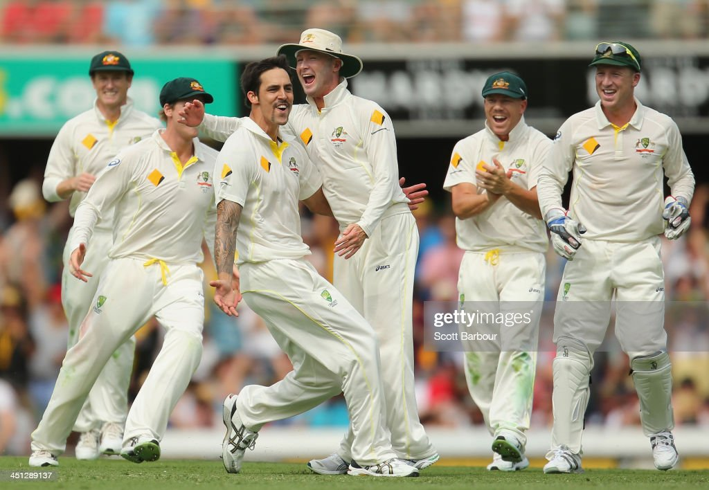 Mitchell Johnson of Australia celebrates with Michael Clarke after dismissing Joe Root of England during day two of the First Ashes Test match between Australia and England at The Gabba on November 22, 2013 in Brisbane, Australia.