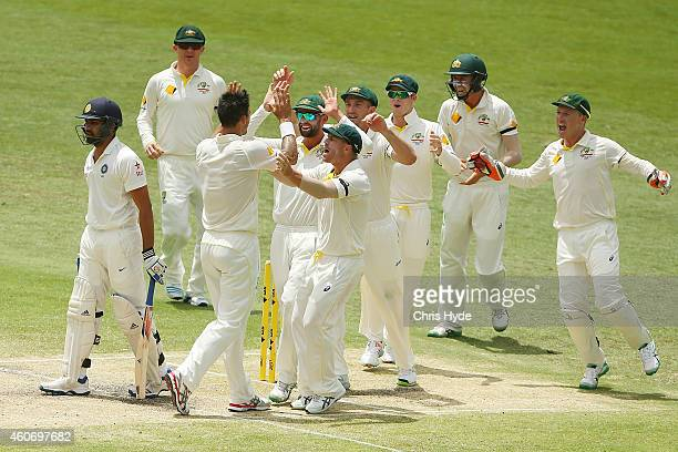 Mitchell Johnson of Australia celebrates with team mates after taking the wicket of Rohit Sharma of India during day four of the 2nd Test match...