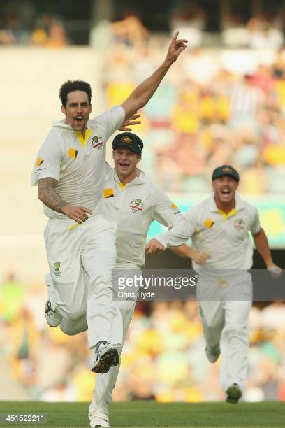 Mitchell Johnson of Australia celebrates with team mates Steve Smith and David Warner after dismissing Jonathan Trott of England during day three of...