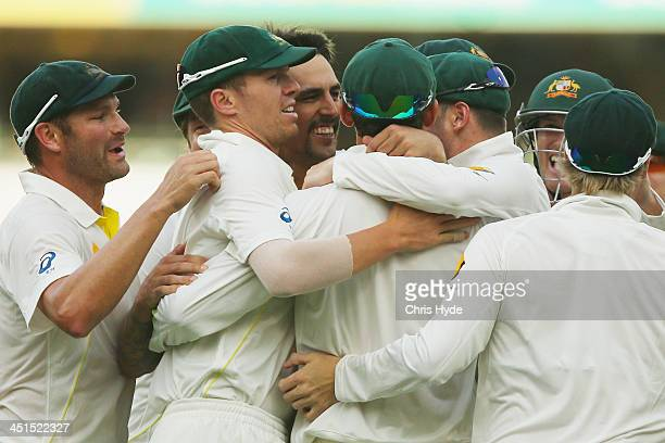 Mitchell Johnson of Australia celebrates with team mates Steve Smith after dismissing Jonathan Trott of England during day three of the First Ashes...