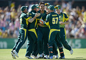 Mitchell Johnson of Australia celebrates with teammates after bowling out England captain Eoin Morgan during the final match of the Carlton Mid One...