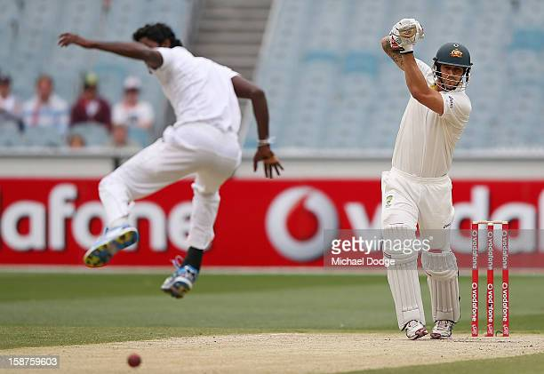 Mitchell Johnson of Australia hits the ball past Shaminda Eranga of Sri Lanka during day three of the Second Test match between Australia and Sri...