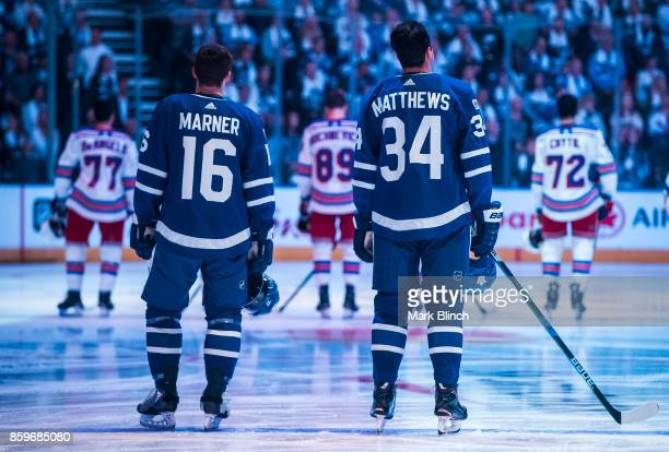 Mitchell Marner and Auston Matthews of the Toronto Maple Leafs stand on the ice for the national anthem prior to the game against the New York...