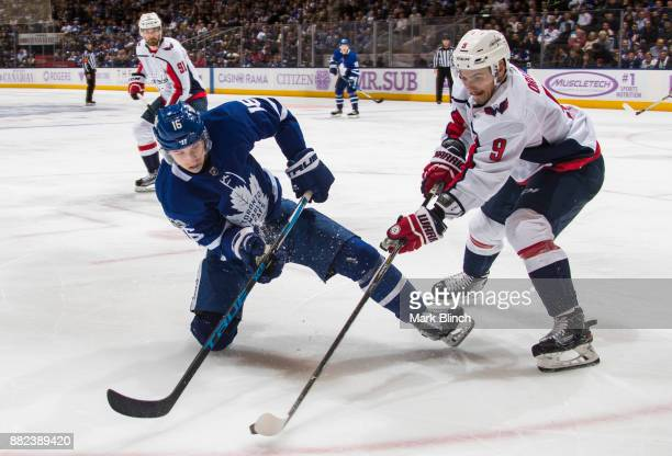 Mitchell Marner of the Toronto Maple Leafs battles for the puck with Dmitry Orlov of the Washington Capitals during the third period at the Air...