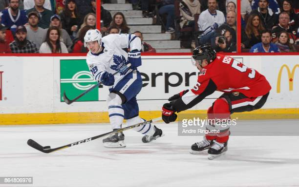 Mitchell Marner of the Toronto Maple Leafs shoots the puck against Cody Ceci of the Ottawa Senators at Canadian Tire Centre on October 21 2017 in...