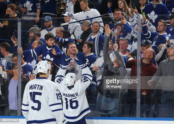 Mitchell Marner of the Toronto Maple Leafs tosses his hockey stick to a fan after their 42 victory against the Buffalo Sabres in an NHL game at the...
