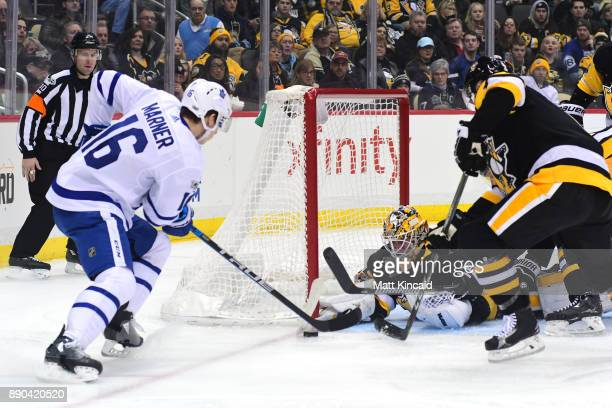 Mitchell Marner of the Toronto Maple Leafs tries to put the puck by Tristan Jarry of the Pittsburgh Penguins at PPG PAINTS Arena on December 9 2017...