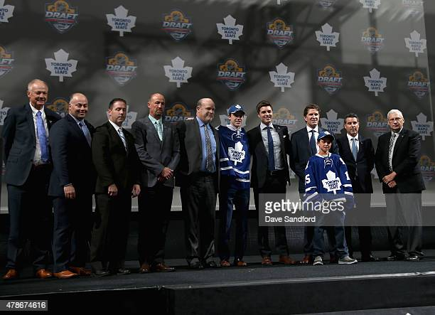 Mitchell Marner poses on stage with team personnel after being selected fourth overall by the Toronto Maple Leafs during Round One of the 2015 NHL...