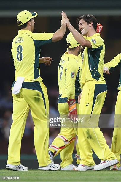 Mitchell Marsh and Pat Cummins of Australia celebrate after Cummins took the wicket of Matt Henry of New Zealand during game one of the One Day...