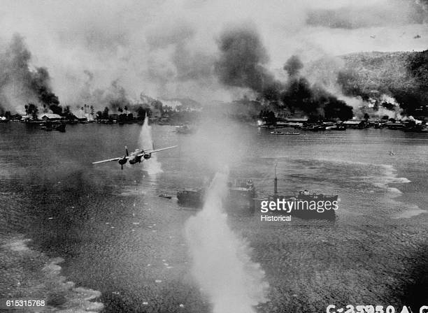 Mitchell medium bomber of the US 5th Air Force attacks a Japanese freighter in Rabaul Harbor Fires caused by US bombers can be seen along the shore...